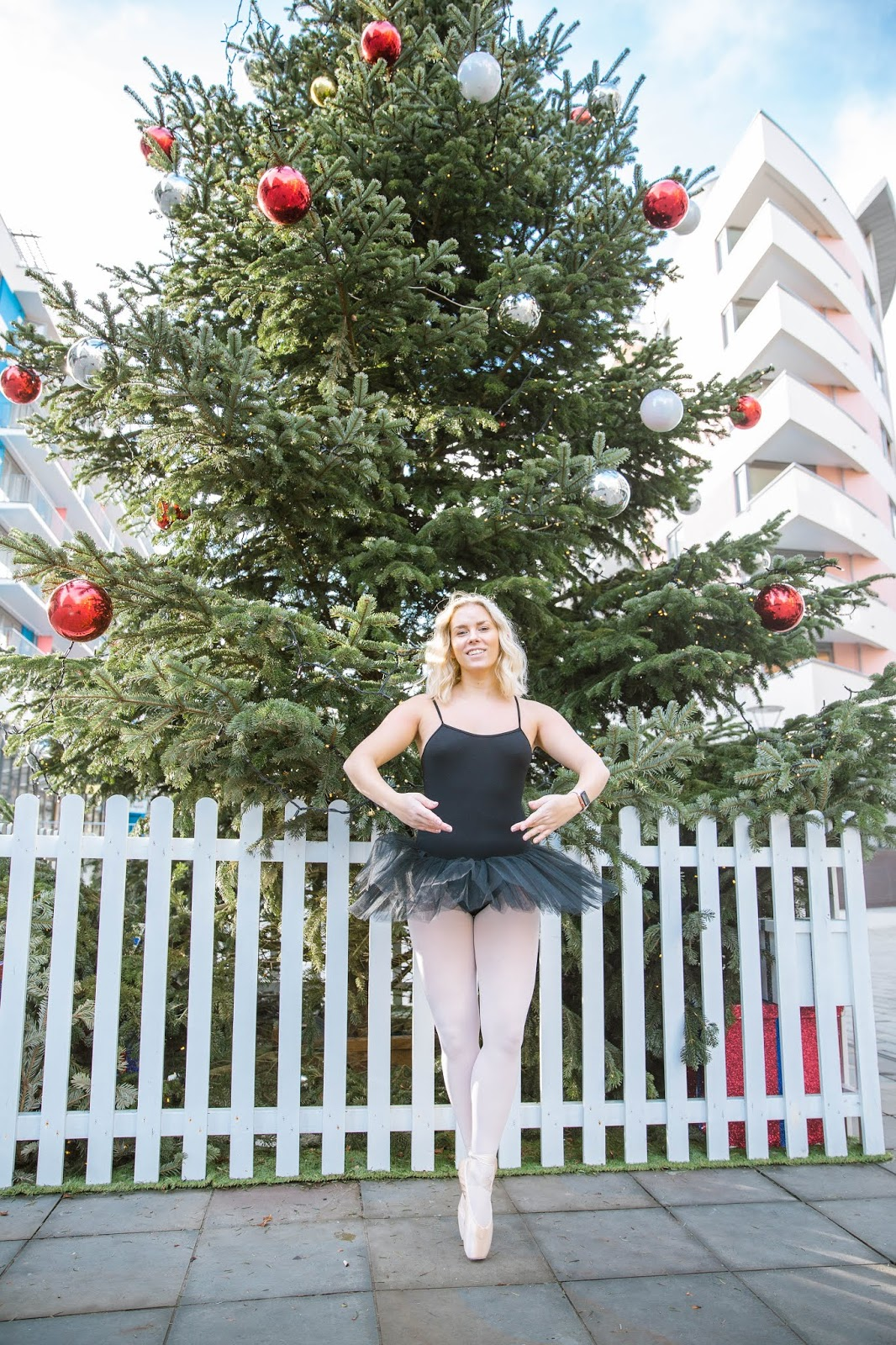 Rachel Emily en pointe in a black tutu in front of a christmas tree ballet - Rachel Emily Blog