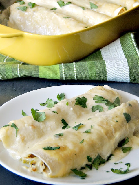Easy Creamy Green Chile Chicken Enchiladas on a white plate