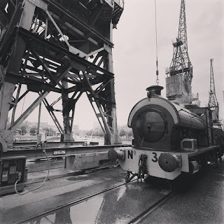 Photo of old cranes and a steam train