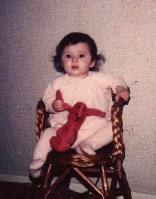 This Little Girl Is Me : a picture of me when I was a toddler, sat on a wicker chair holding a red soft toy bunny
