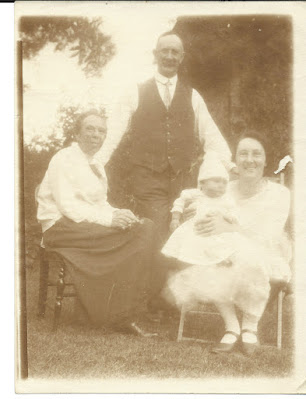 Elderly lady seated besides her daughter also seated with baby. Grandfather standing behind