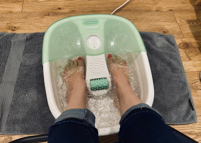 Feet in a foot spa before reflexology treatment
