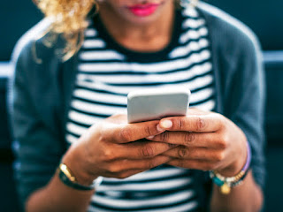 Blurred image of a woman who is olive skinned and has blonde hair and is wearing pink lipstick and a striped top the photographed is focussed on the mobile phone in her hands