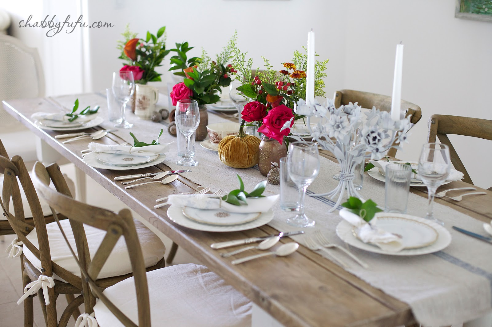 Thanksgiving Beach House decor - tablescape with white cloth runner and bright fall flower centerpieces