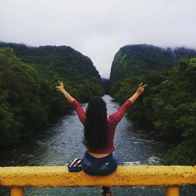 mujer con los brazos abiertos desde el puente del río fraguita