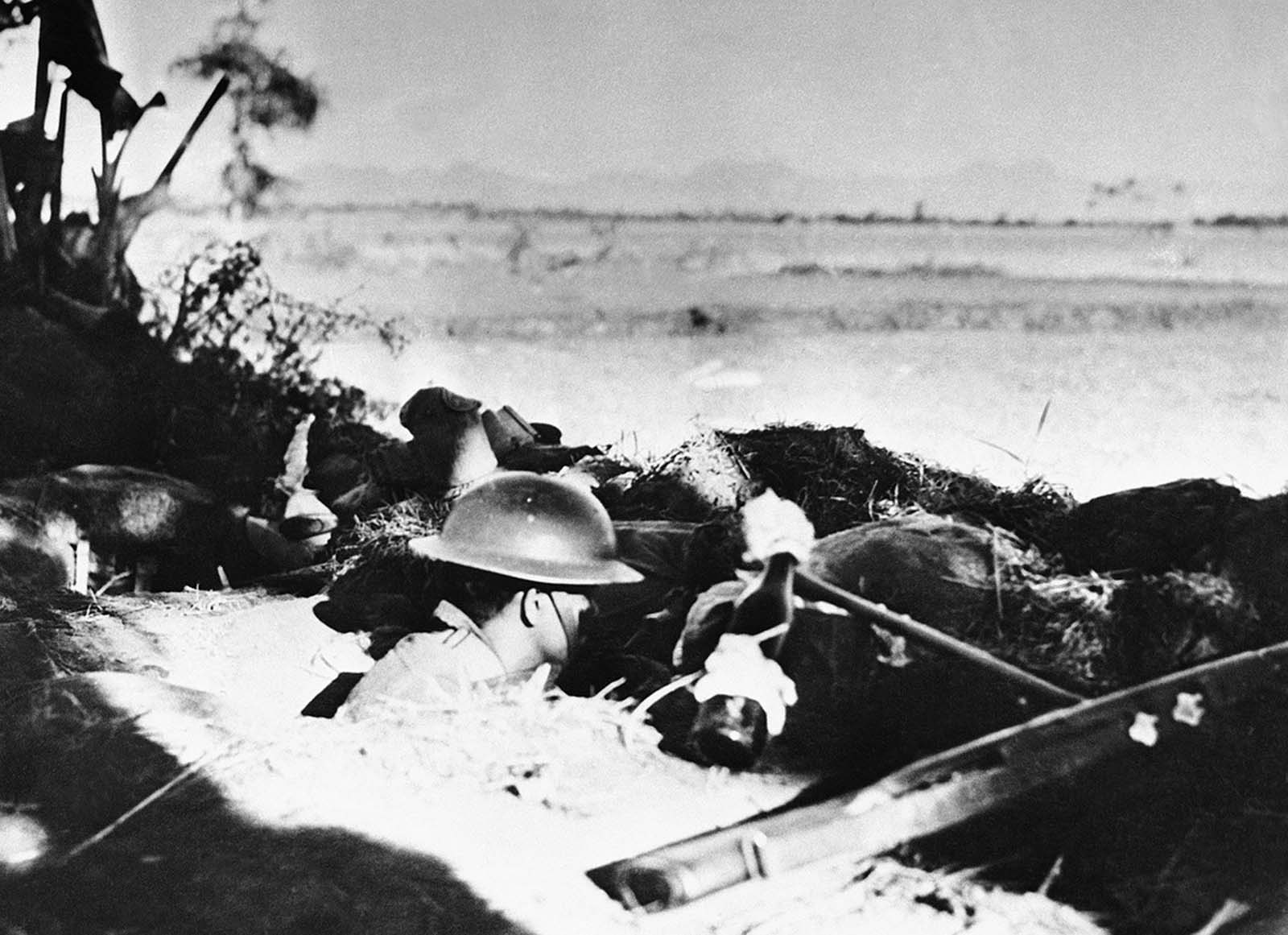 An American soldier stands tense in his foxhole on Bataan peninsula, in the Philippines, waiting to hurl a flaming bottle bomb at an oncoming Japanese tank, in April of 1942.