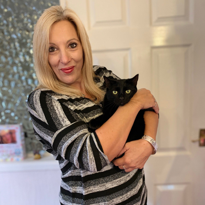 blonde woman in stripy black and grey top holding black cat
