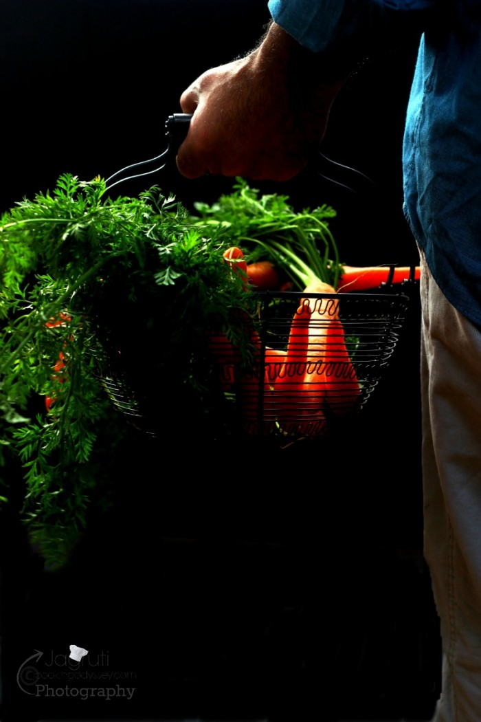 A man holding green-topped carrots in a basket.