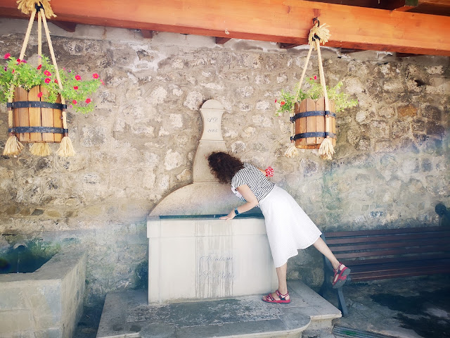 Donna di spalle con gonna bianca e maglie a righe che beve alla fontana