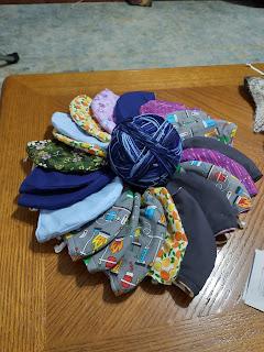 Panel masks arranged in a wreath around a ball of blue yarn
