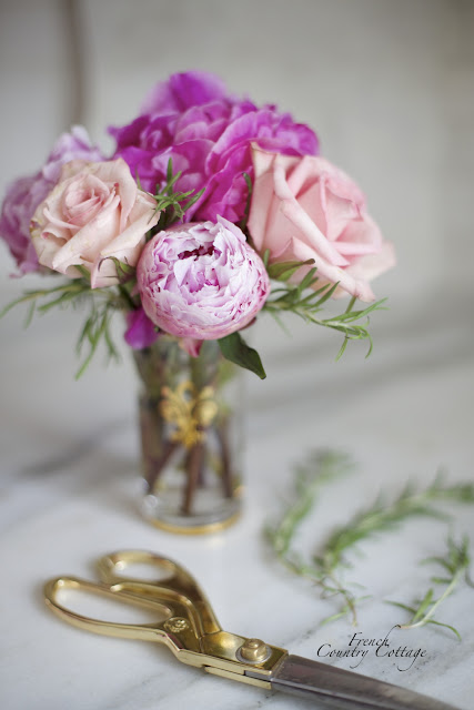 Peonies and roses on counter with herbs and gold scissors