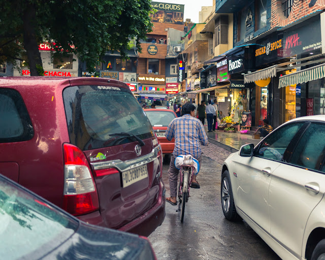 man riding bicycle among cars in the monsoon in khan market new delhi india