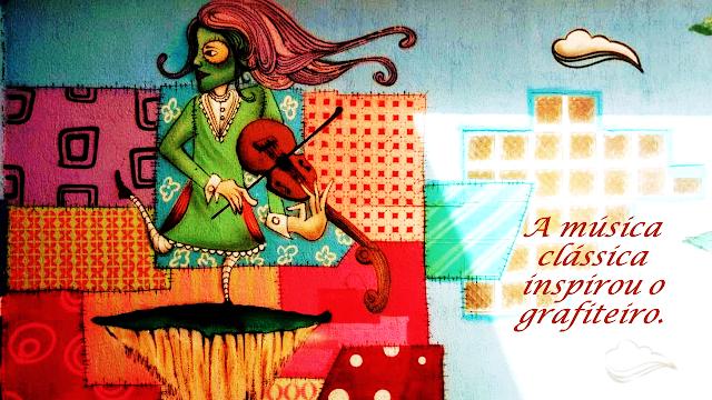 Quadro de uma pintura em grafite de uma pessoa tocando violino.  A imagem mostra uma pintura em grafite de uma pessoa certamente um músico, tocando um instrumento musical o violino. A pintura tem traços bem definidos e coloridos que mostram claramente o pensamento do artista do grafite.