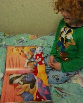 4 year old reading bedtime blanket book