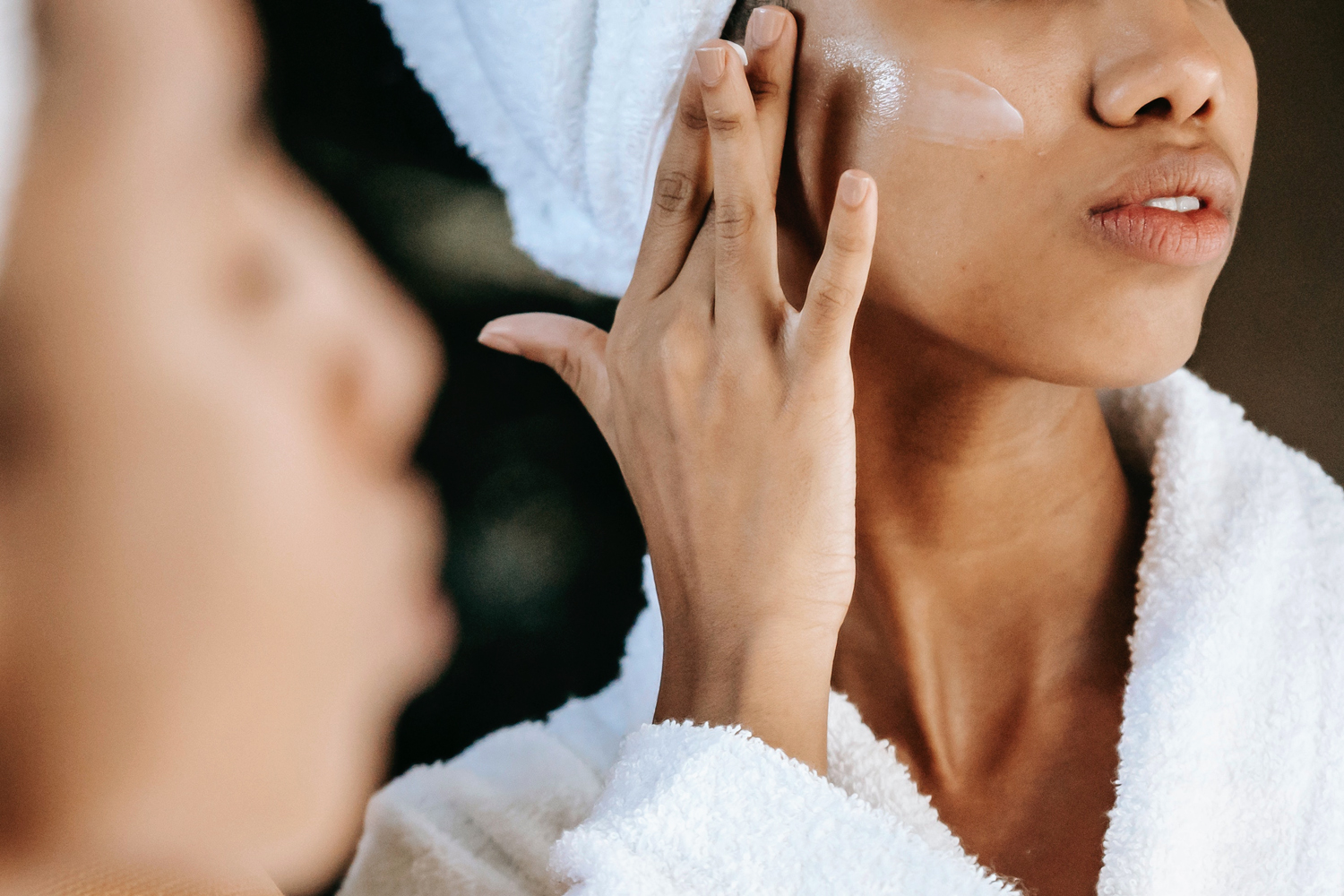 woman in front of the mirror taking care of her face skin