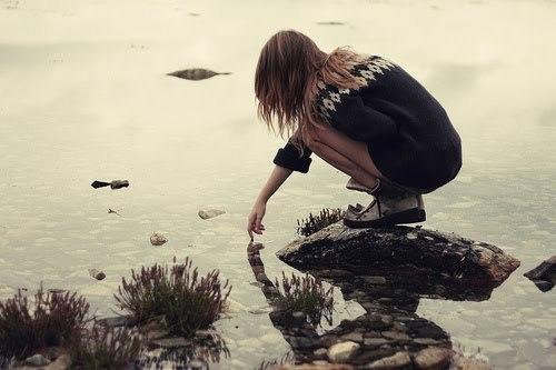 garota numa pedra no lago com os dedos na água