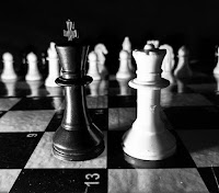 Black king and white queen chess pieces.
