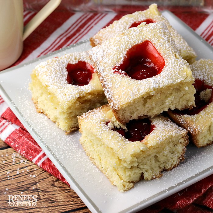 Shelly's Cherry Squares by Renee's Kitchen Adventures stacked on a white plate with a red and white napkin in the background