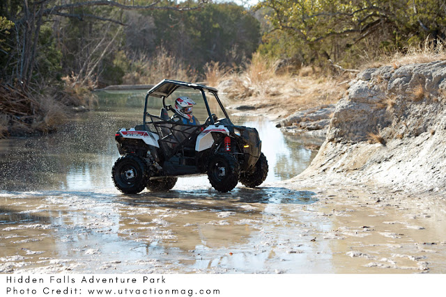 ATV rider moving through shallow muddy water