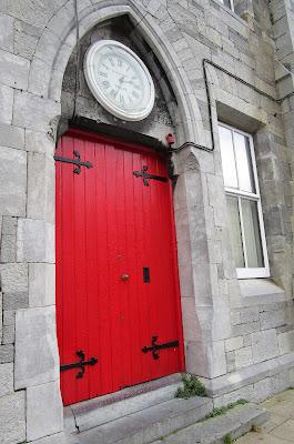 punainen ovi, kello, kiviseinä
