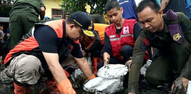 Anies Bantu Warga Makasar Pungut Lumpur Sisa Banjir