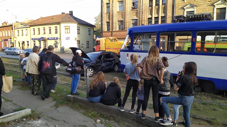 Cilvēki vēro tramvaja un vieglā auto avārijas sekas