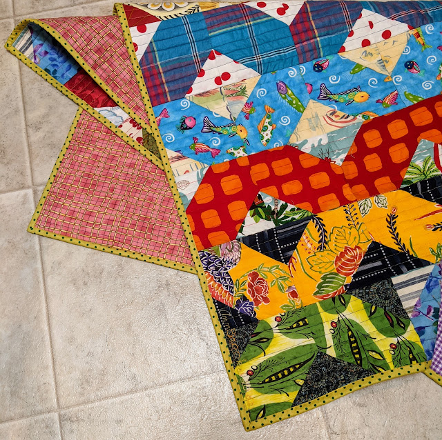 Folded quilt shows detail of the front, back,,binding, and quilting design