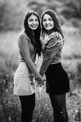 BLACK AND WHITE Teenage sisters holding hands posing for Christmas mini sessions with Morning Owl Fine Art Photography located in San Diego.