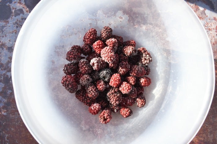 Frozen blackberries in clear bowl