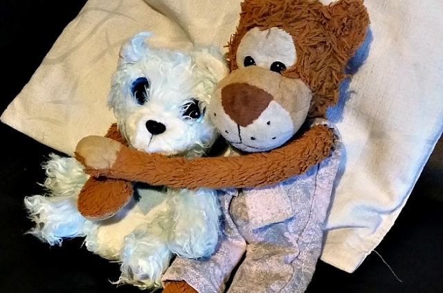 2 soft toys. A monkey and a blue polar bear