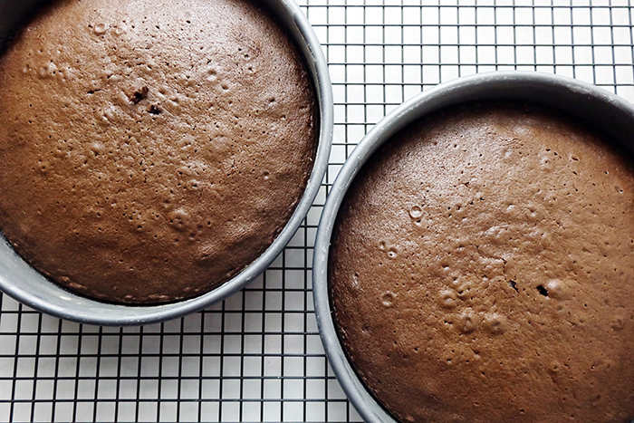 baked cakes cooling in pans on rack