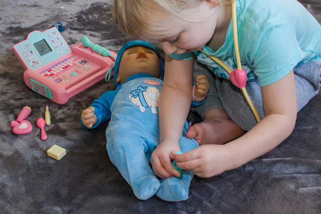 A child giving Baby Annabell Alexander doll a pretend injection with a medical set