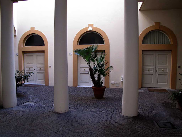 Three doors, inner court of a building in via Roma, Livorno