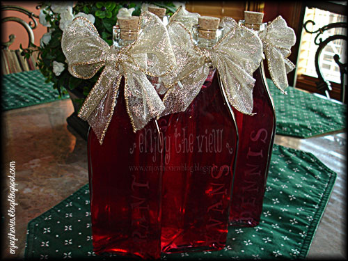 bottles of homemade raspberry vodka with metallic gold bows and etched names