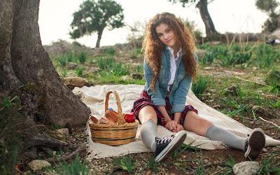 Chica colegiala sentada en el parque con cesta de comida