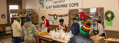 volunteers serve holiday meals to guests
