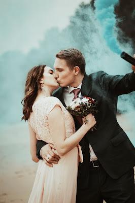 Pareja de novios posando mientras se besan con una antorcha de humo de color azul