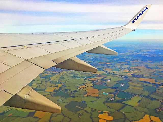 Wing of a RyanAir plane flying over the Romanian countryside