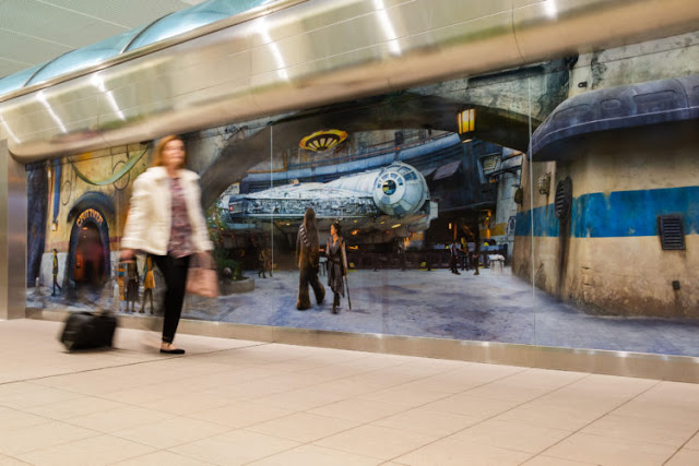 A traveler at Orlando International Airpott in Orlando, Fla., passes by a scene from Star Wars: Galaxy's Edge at Disney's Hollywood Studios prior to boarding a shuttle to the Main Terminal, Nov. 16, 2019. Disney installed these artistic wraps on the shuttle stations to immerse airport travelers in scenes from Star Wars: Galaxy's Edge.