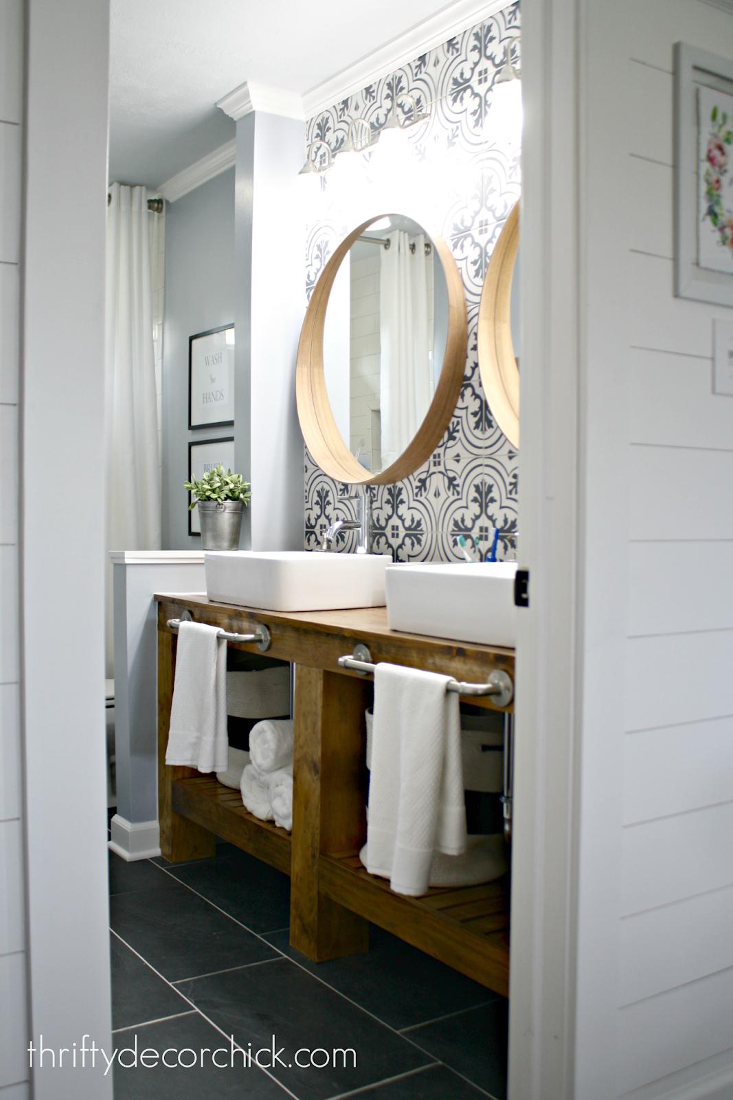 black and white tile behind wood vanity bathroom