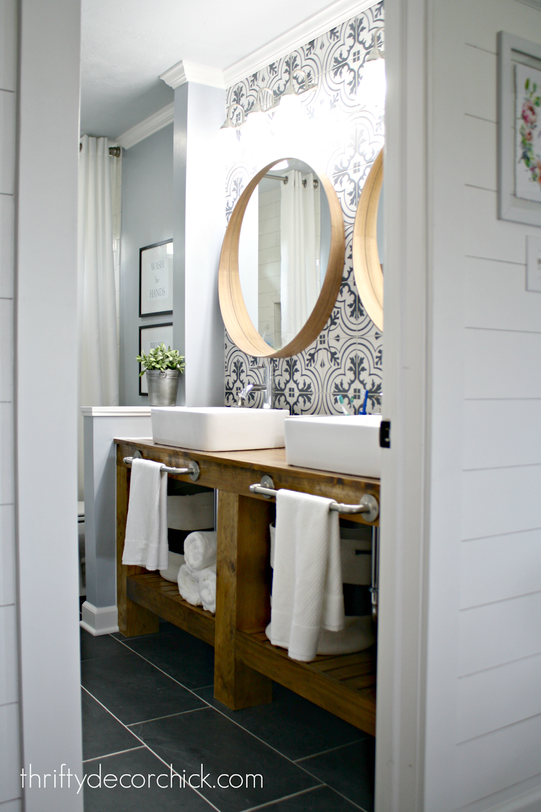 black and white tile behind wood vanity bathroom