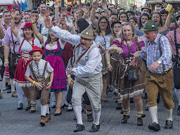 A crowd of people in a German festival enthusiastically having a good time together