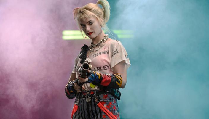 Imagem: a personagem Arlequina, uma mulher muito pálida com cabelos loiros em trancinhas pintadas de rosa e azul, uma camisa rosa com Harley escrito em preto, shorts jeans listrados e segurando um espingarda ou escopeta que atira tinta, e por trás dela um fundo de fumaça rosa e azul.