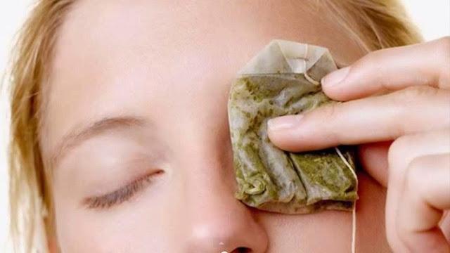 Mujer con una bolsa de té para eliminar ojeras.