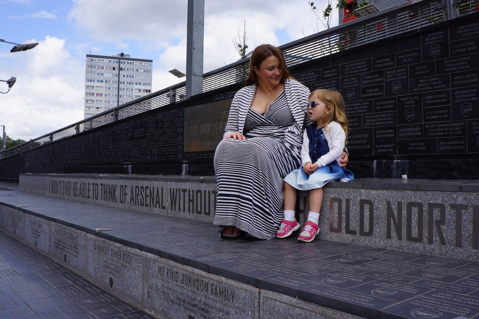 mother and daughter sitting on emirates stadium steps
