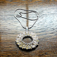 circular quilled pendant with silver necklace chain displayed on wooden table