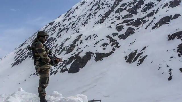 Indian army trooper stands guards the snow-cleared Srinagar-Leh highway in Zojila, 108 KM far from Srinagar.