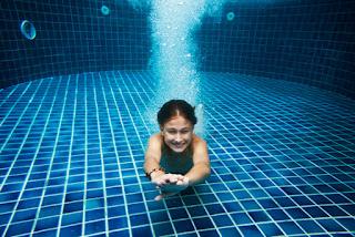mulher mergulhando na piscina azul