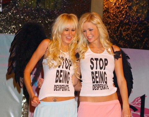 """Paris Hilton and Kimberly Stewart wearing the 'STOP BEING Desperate"""" matching top during a party at the Palms Casino and Hotel in Las Vegas back in April 2005.  PYGear.com"""