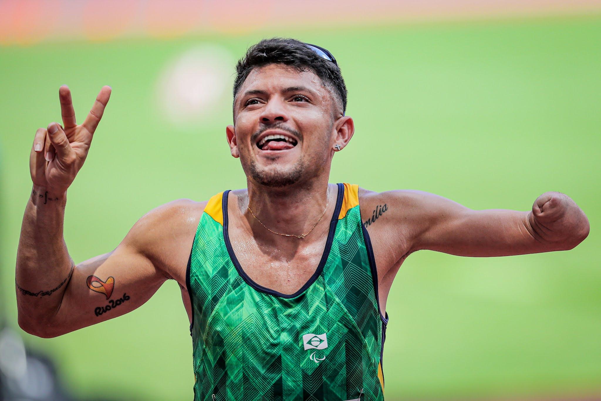 Petrúcio Ferreira, de uniforme verde, sorri e mostra a tatuagem no muque esquerdo